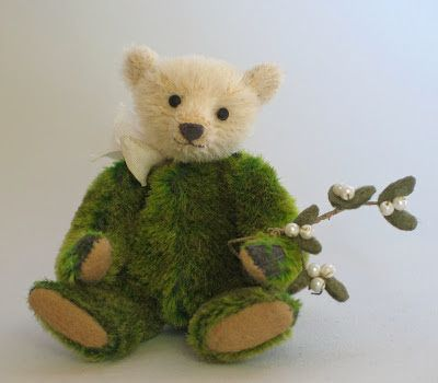 "Paula Strethill-Smith. Mr Mistletoe is 3.5"" miniature teddy bear created from antique mohair in faded green with dark grey backing cloth. His face is in ivory mohair with a wobble neck joint and matt eyes. This festive little chap is already for Christmas parties as he carries his tiny sprig of felt with pearl mistletoe just waiting for a kiss."