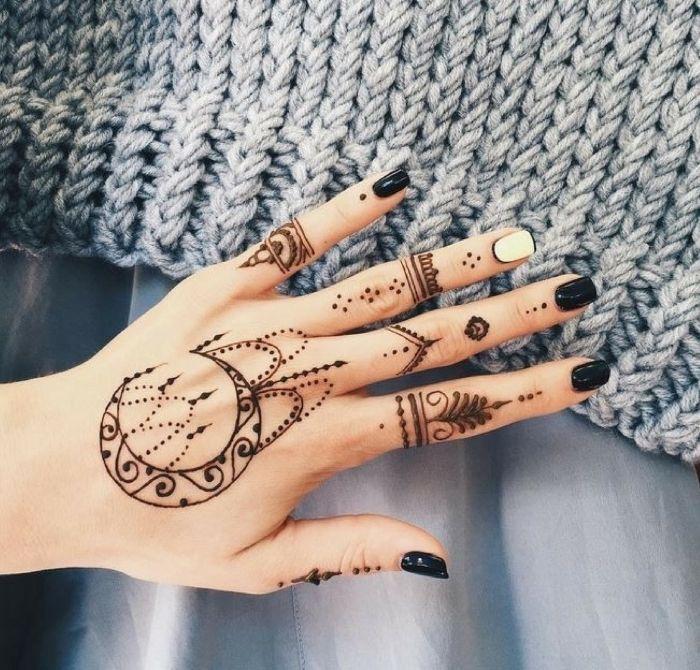Schwarze Henna-Tätowierung an Hand, schwarzer Nagellack