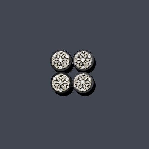 ONYX AND DIAMOND CUFF LINKS, CARTIER, ca. 1920. Platinum. Very decorative, fine twin cuff links, each of 1 round onyx plate with appliquéd, geometrically open-worked flower motif, set throughout with numerous old European cut diamonds. Signed Cartier, French platinum mark. Ca. 1.4 cm Ø. With case.