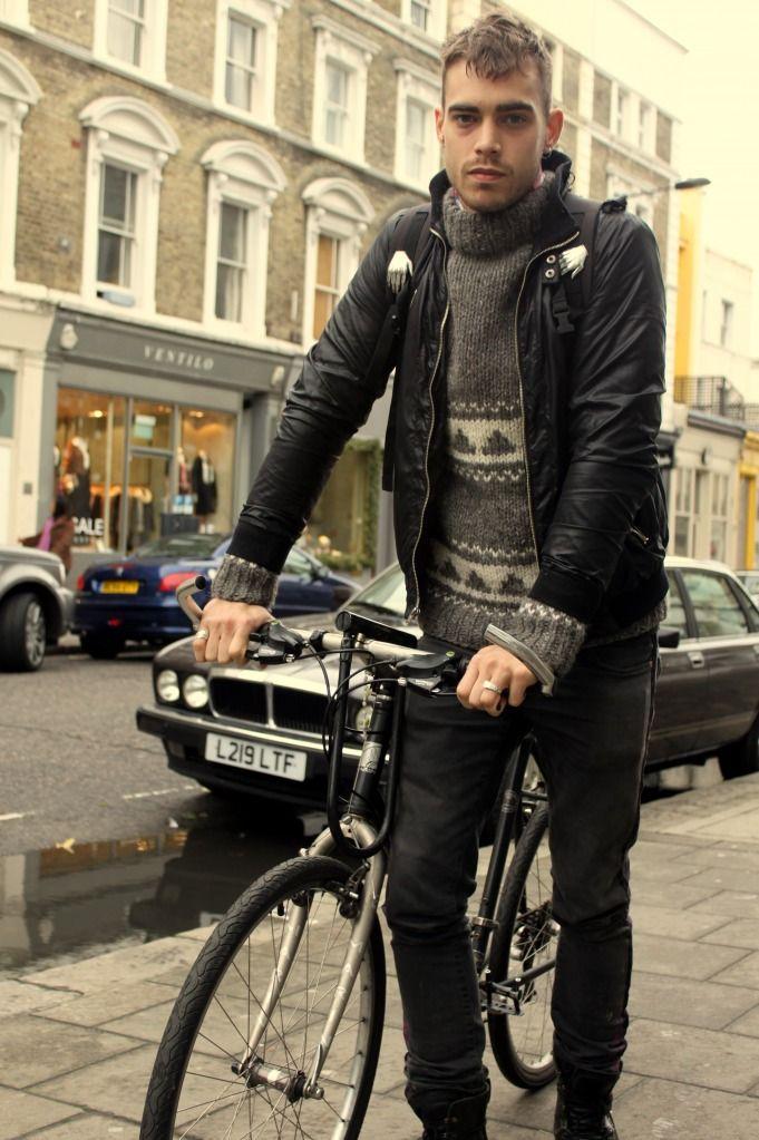 Notting Hill es uno de los barrios más fashionistas de Londres.  Aquí la moda en asociación con el ambiente artístico y algo bohemio,  no solo acoge la elegancia más ortodoxa, sino el estilo entendido en todas sus variantes, lo que hace de este barrio un lugar  sin duda ecléctico.    En esta ocasión, nuestro ciclista hace guiños al punk con sus Dr. Martens, sus pitillo, cazadora de cuero negra y un peinado del que se intuye una cresta. El jersey jaquard es un clásico que no pasa de moda, si…