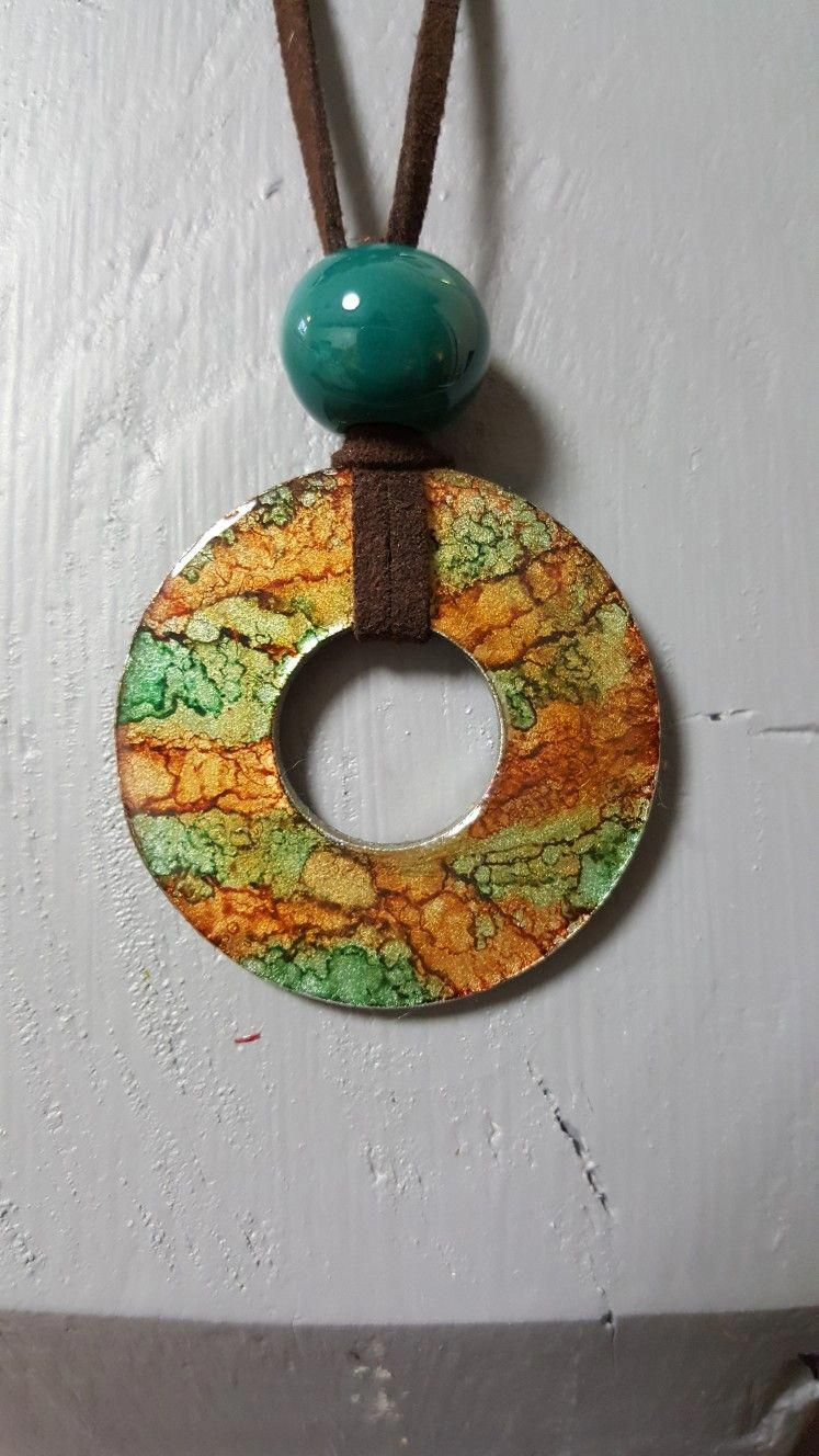 Washer pendant with alcohol ink. Finished off with cording and a bead. #diyjewelryideas #alcoholinkcrafts