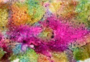 By Trish Bee. Splash & dot alcohol inks on glossy cardstock. Spray piece with spray starch. Add inks & spray again, & perhaps a third time, until you get the look you want. At this point, you can choose to use the piece as a background or lay another piece of glossy cardstock (glossy side down) over the top, rub gently, peel, and make two background pieces.