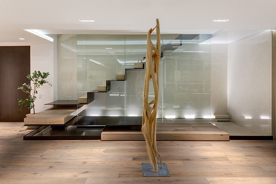 Sculptural floating staircase above pool of water in the living area