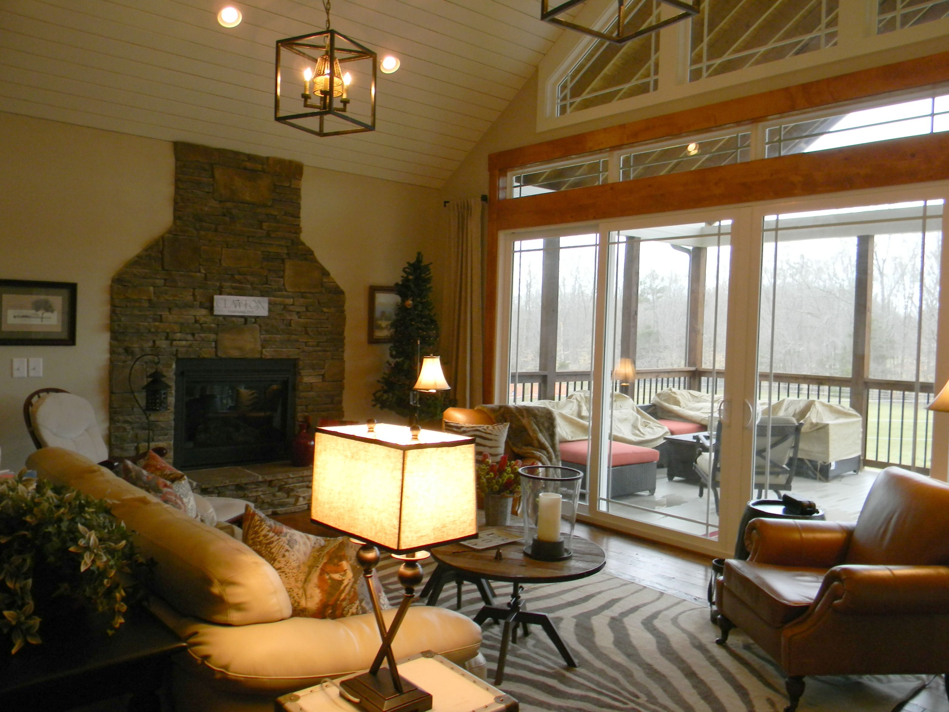 One of the living areas in the house with a gorgeous fireplace and big windows looking out into the backyard and farm.