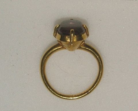 England 14th/15th century Gold ring, oval bezel set with a balas ruby of purple hue held in four claws.