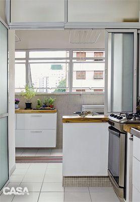 cozinha integrada a uma pequena área de serviço, os armários são de laminado com moldura de madeira nas portas