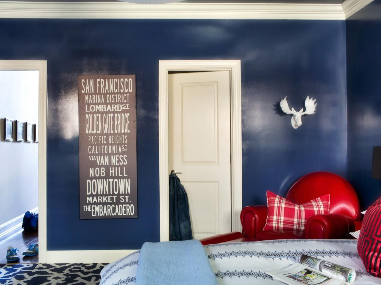 the navy blue walls in this eclectic bedroom are given a custom