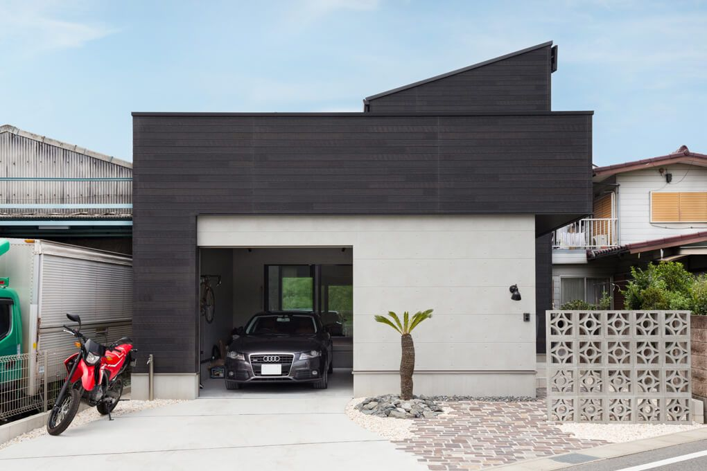 無機質なコンクリート調の外壁にダークブラックの木目調の外壁を合わせ