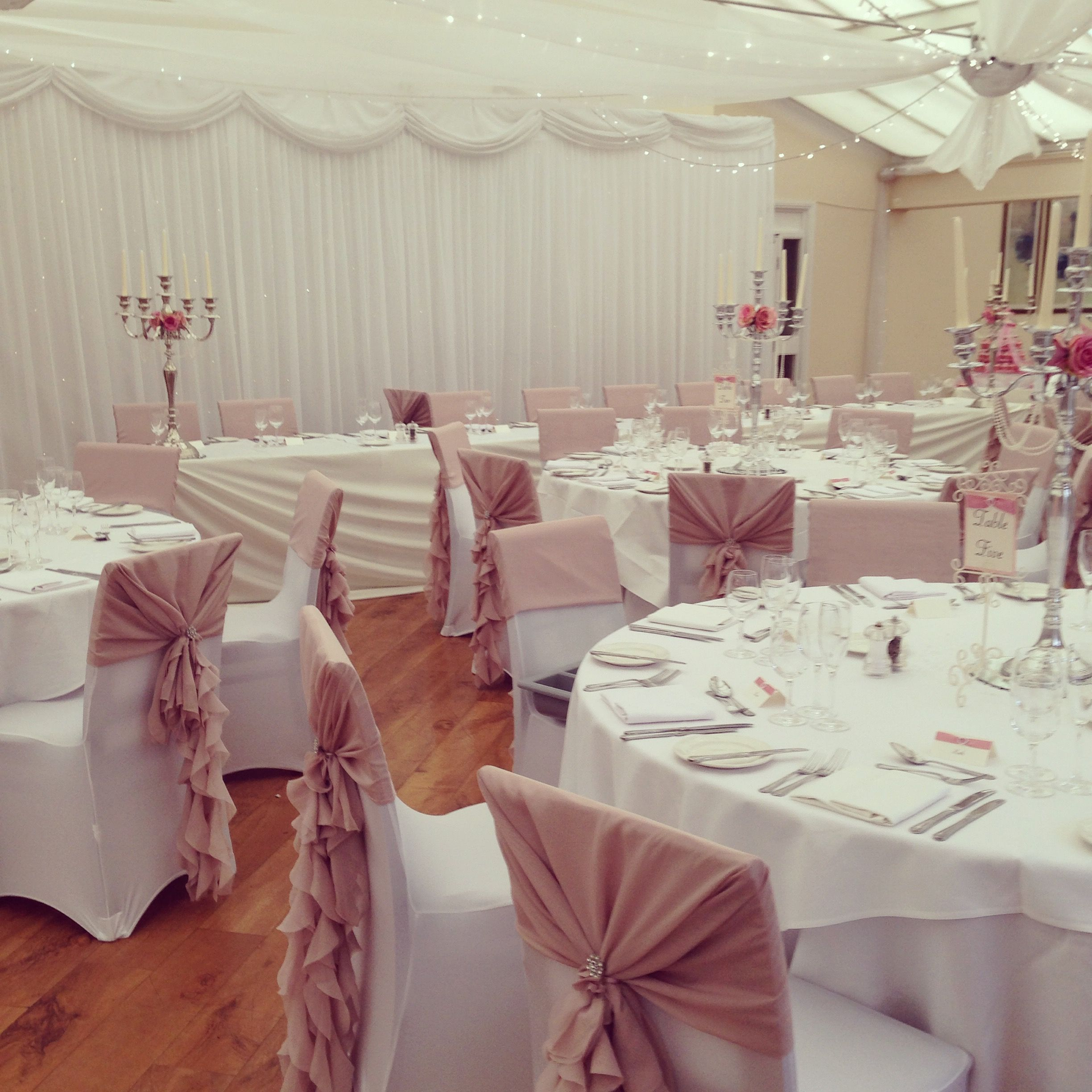 Wedding Chair Covers Yeovil White Parson Slipcovers Dusky Pink Ruffle Hoods With Diamante Brooches Over Candelabra Centrepieces Decorated Roses And Pearl Garlands