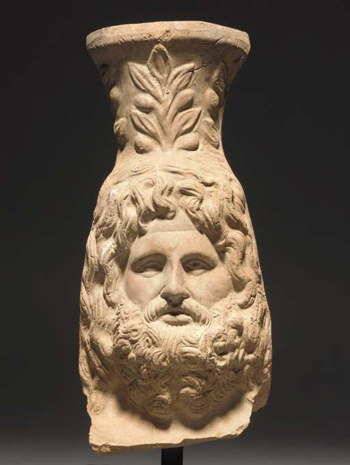 Roman Egyptian terracotta head of Zeus Serapis, 1st century B.C.-1st century A.D.  Hollow moulded, the bearded god wearing a modius on his head, 22.8 cm high. Private collection
