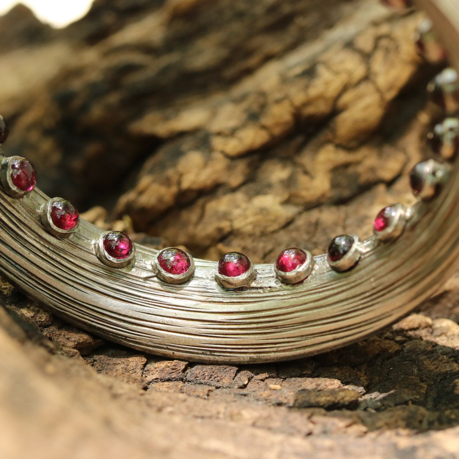 Silver cuff bangle bracelet with garnet cabochons set inside the bangle