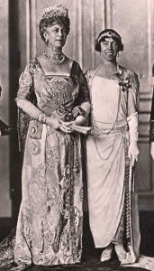 Queen Mary, consort of George V with Queen Elisabeth of Belgium in the 1920s. While the Queen of Belgium sports bobbed hair, a sleeveless dress and a boyish silhouette in the fashion of the time, Queen Mary still wears her long hair coiled in the Edwardian style with a floor length, hourglass shaped dress.