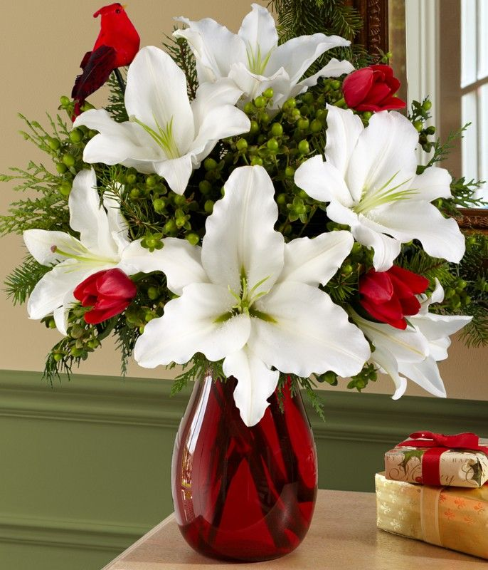 Floral Centerpiece ~ White stargazer lilies and red roses in a red vase.