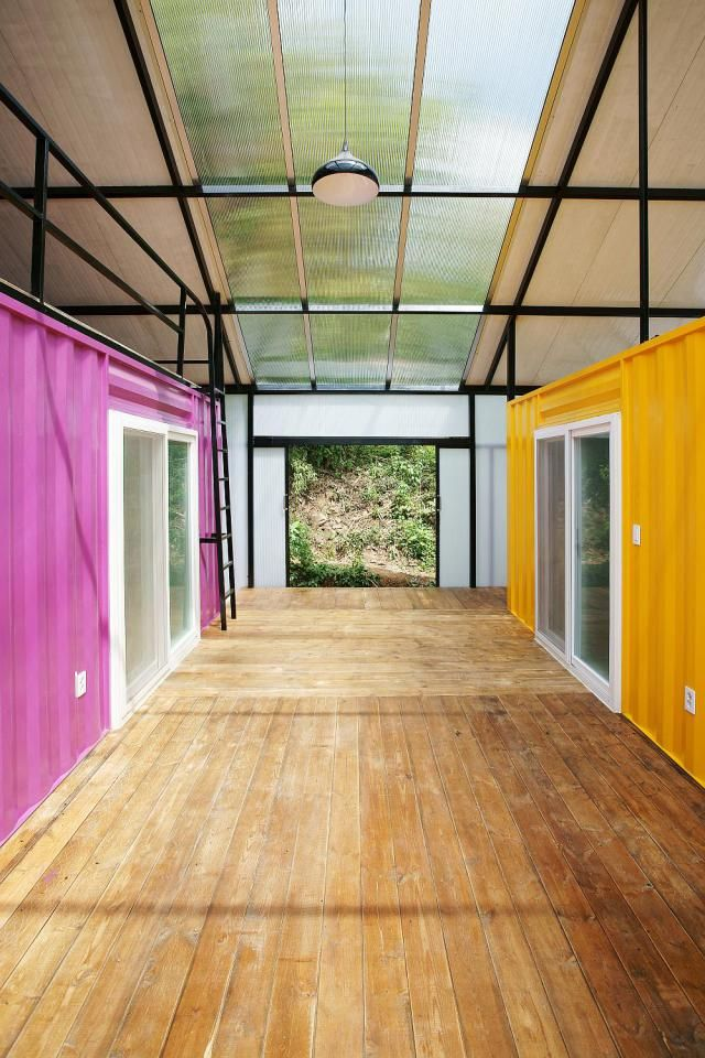 This low-cost shipping container house is covered by a tent-like  polycarbonate structure