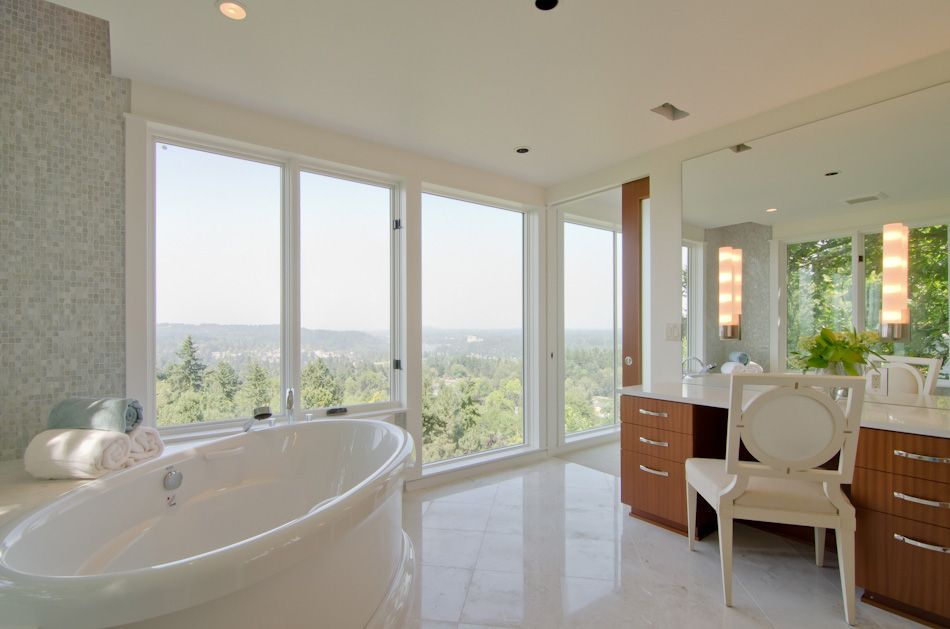 Free standing tub, marble floors and reflective tile add to the open feeling of this master bath.