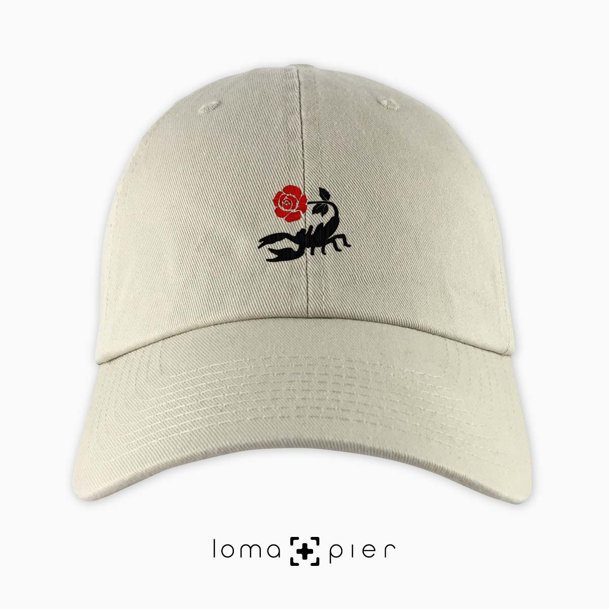 c39973cc78e64 SCORPION ROSE icon embroidered on a khaki unstructured dad hat with red and  black thread by loma+pier hat store made in the USA