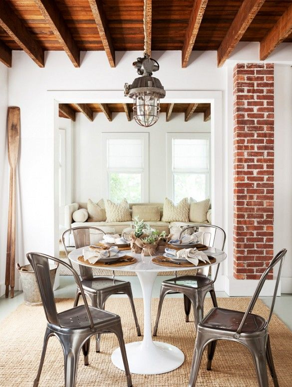 Quaint Dining Area With Exposed Brick Bead Board Ceilings Wood Beams And Metal Chairs Surrounding A White Circular Table