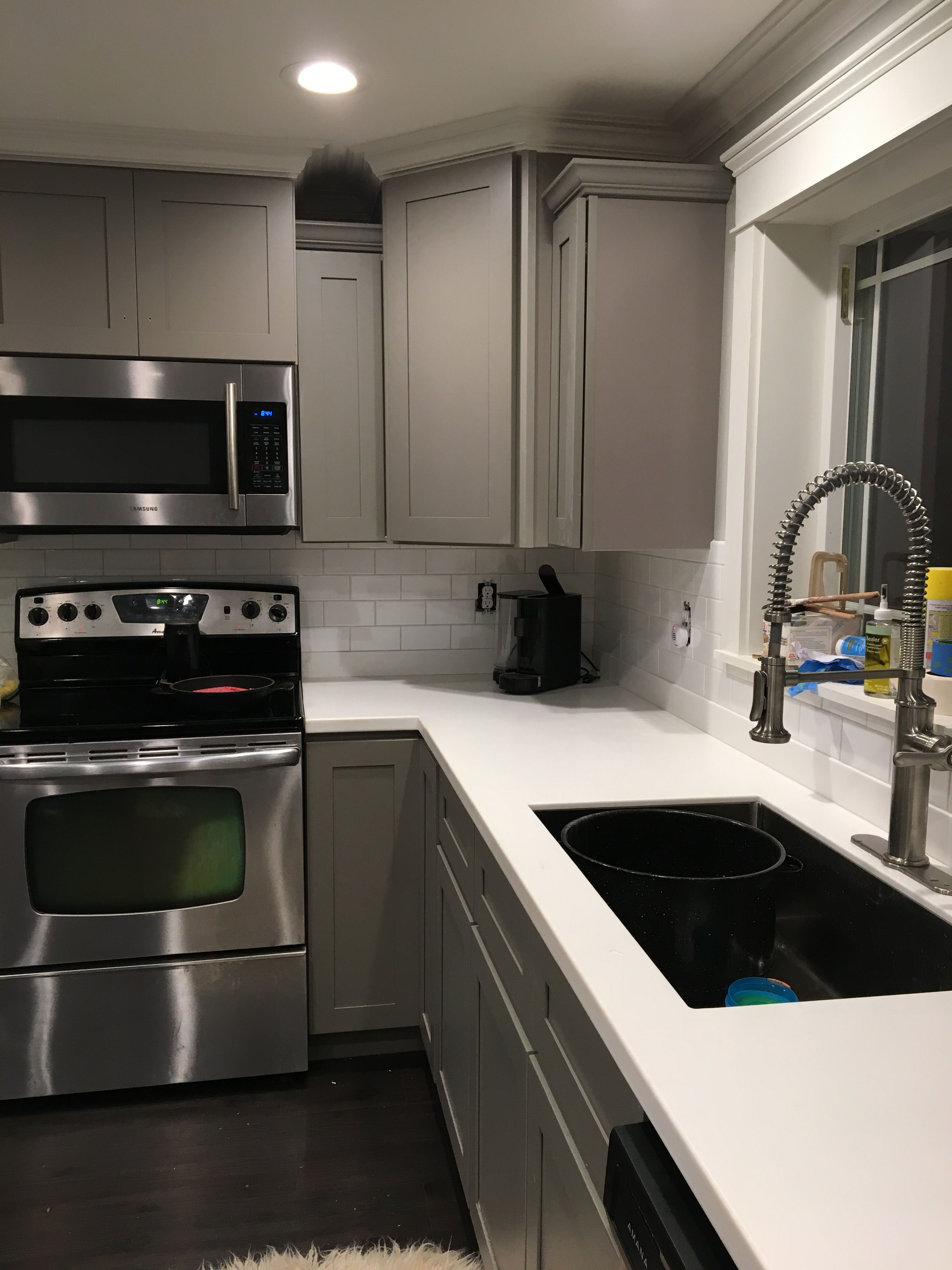Grey kitchen cabinets with solid surface counter added subway tile and crown molding around ceilings also gray glass tiles quartz countertop farmhouse sink