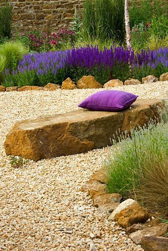 Gravel garden with rock seat, purple cushion and Salvia 'Wesuwe'