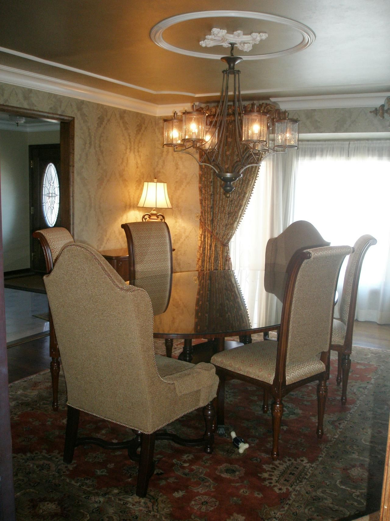 Different trim treatment than others this elegant dining room is this elegant dining room is furnished with a oval wood table fabric covered high back chairs patterned drapery and a low hanging chandelier arubaitofo Gallery