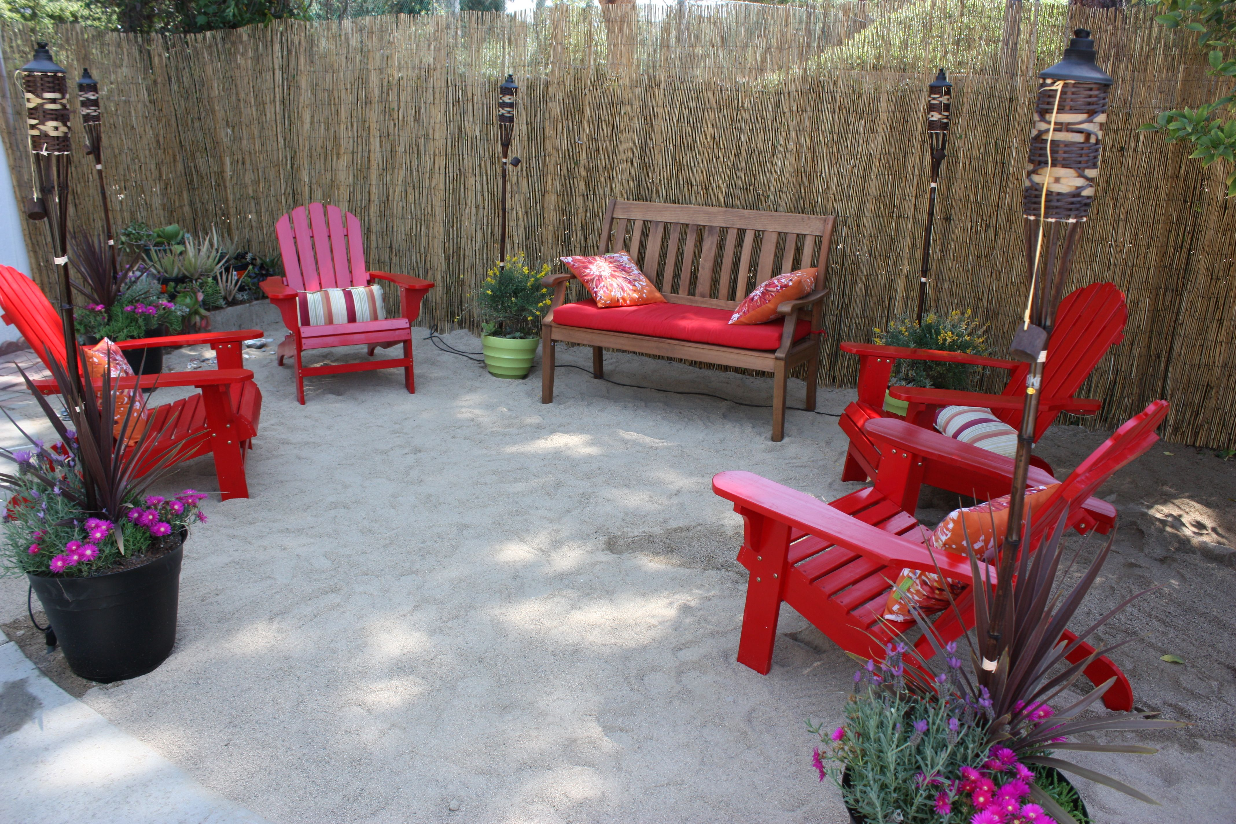 Backyard Paradise: Red Adirondack Chairs On Backyard Beach