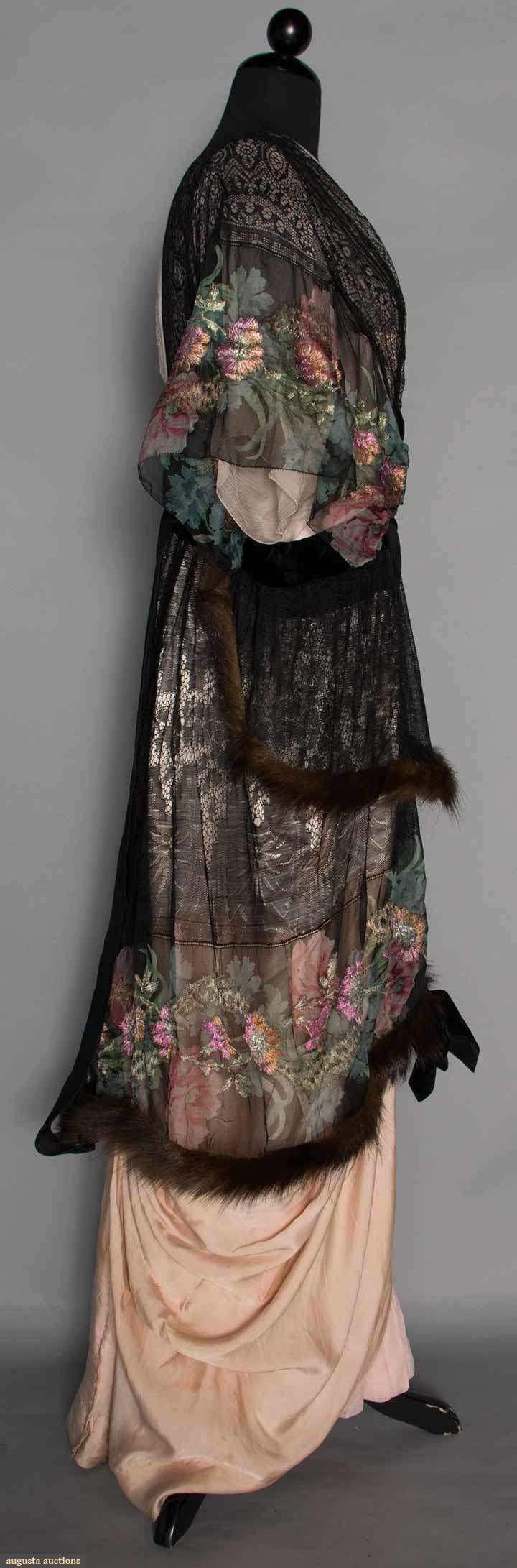 PRINTED LAME EVENING GOWN, c. 1913. Gown of floral printed & lame brocaded chiffon w/ black lace, short kimono sleeves, 2 fur trimmed chiffon & lace skirt tiers, black velvet bow trims, narrow draped pale pink underskirt. Sideway