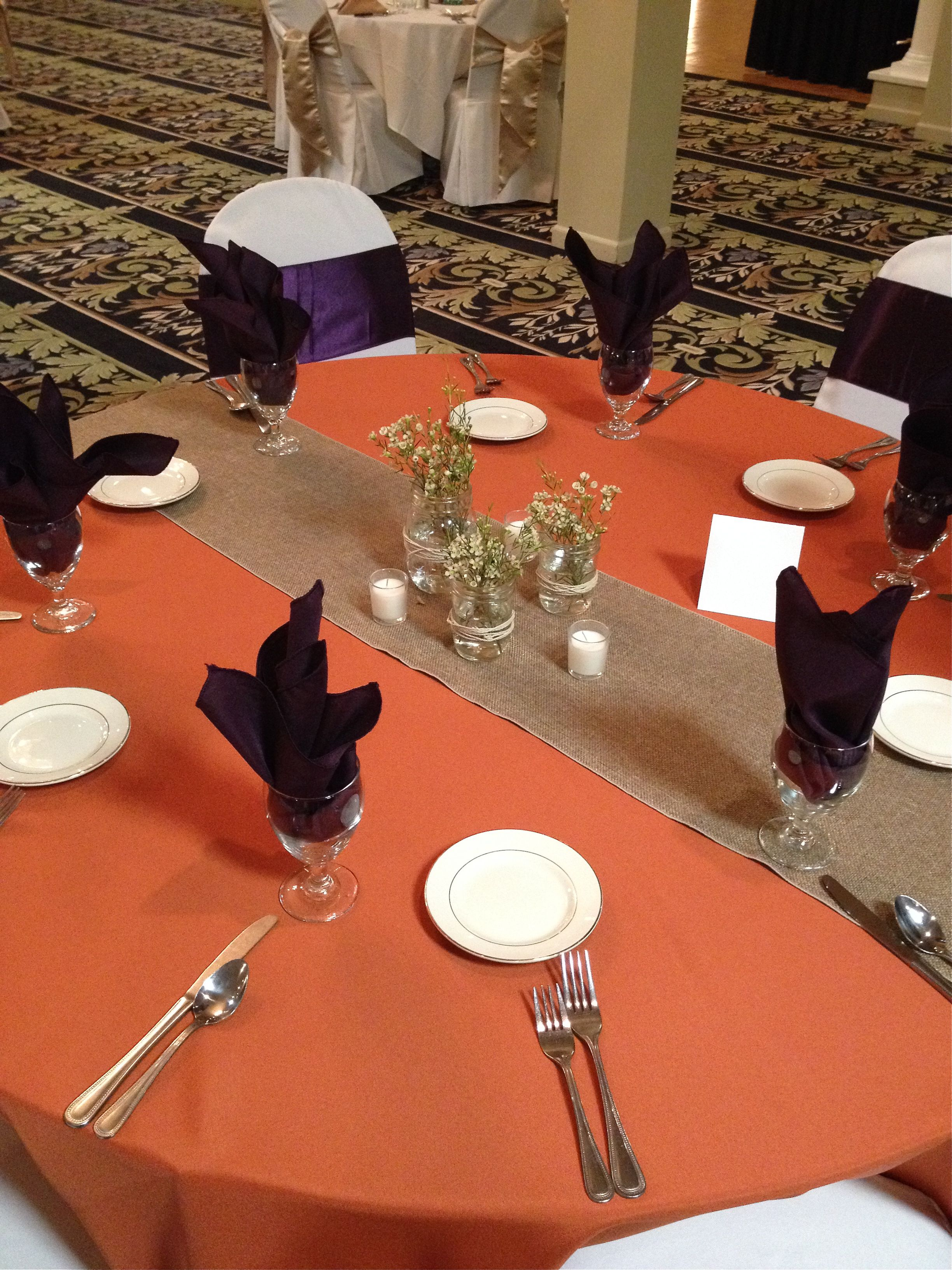 Wonderful Burnt Orange Table Cloth With Burlap Runner And Plum Napkins In The Glasses.
