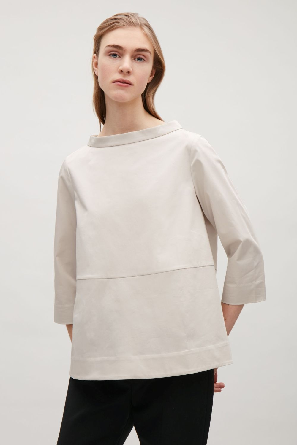 Made from crisp fabric with a slight-stretch, this top has a wide neckline with a standing collar. Fitted on the shoulders, it is a flared shape with 3/4 sleeves and buttons along the back.