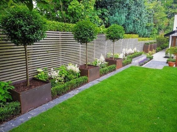 A) Evergreen trees in metal boxes B) Lavender plants / bushes in between C) How is best to edge this area (separating lawn and flowers) D) Which evergreen trees are cheapest? And easy to maintain #amazing garden ideas #diy tropical garden #dream garden #garden hot tubs #rooftop garden #secret garden #small tropical garden #tropical garden ideas