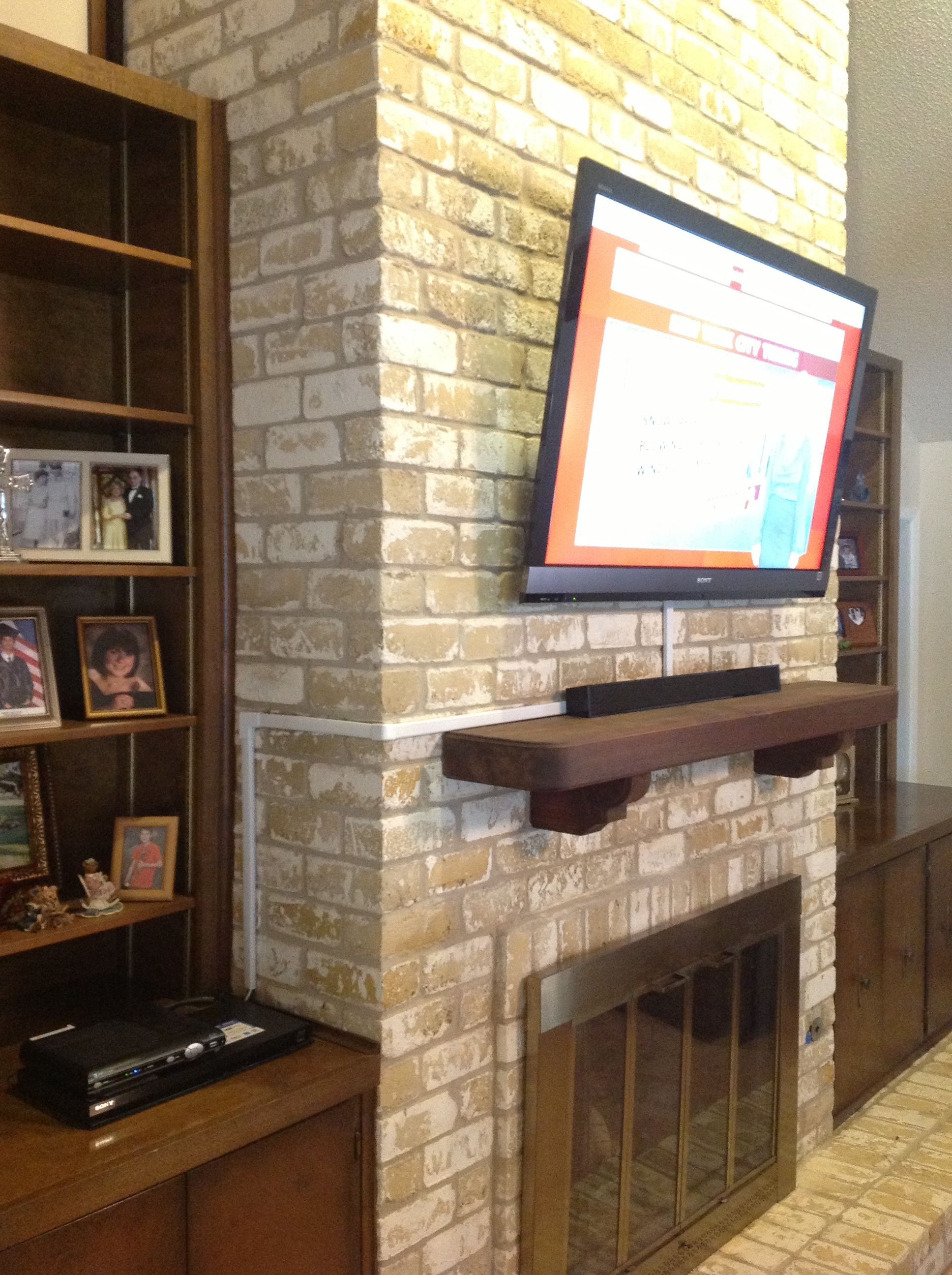 tv wall mounting over a brick fireplace by ernesto vesta fireplace rh pinterest com installing tv on brick fireplace mount tv on brick fireplace