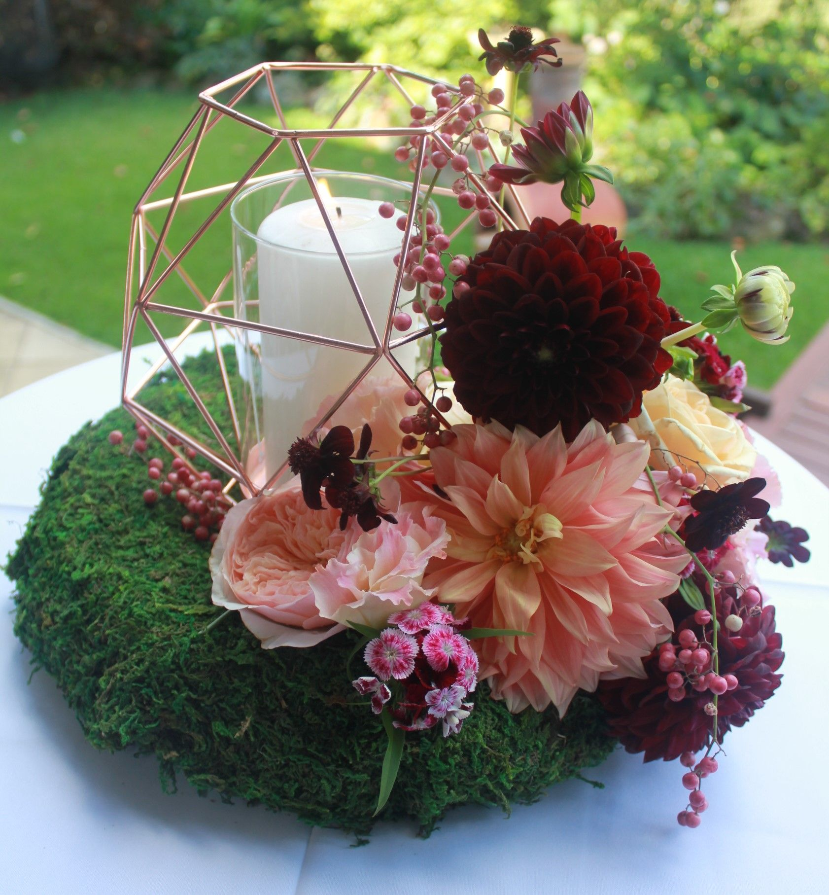 Geometric Copper candle holder with autumn tone flowers, Dahlia, David Austin Roses, Pepper Berry & Cosmos. Created by Poppies and peas Floral Design