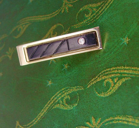 This is a very handsome black tie clip with a brilliant rhinestone. This tie clip is in good vintage condition, well made and medium weight.
