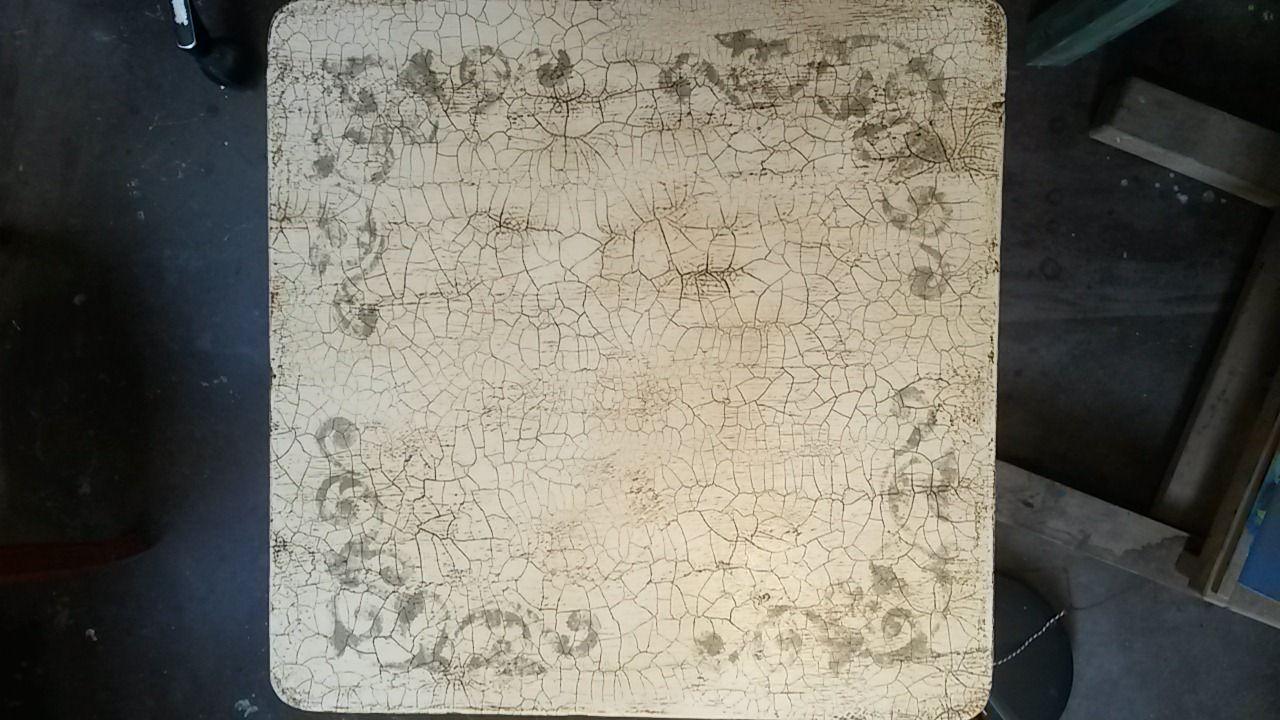 Werken met craquele. Het bovenblad van een tafeltje, beschilderd, sjablonen erop gezet en daarna behandeld met een craquelemedium.