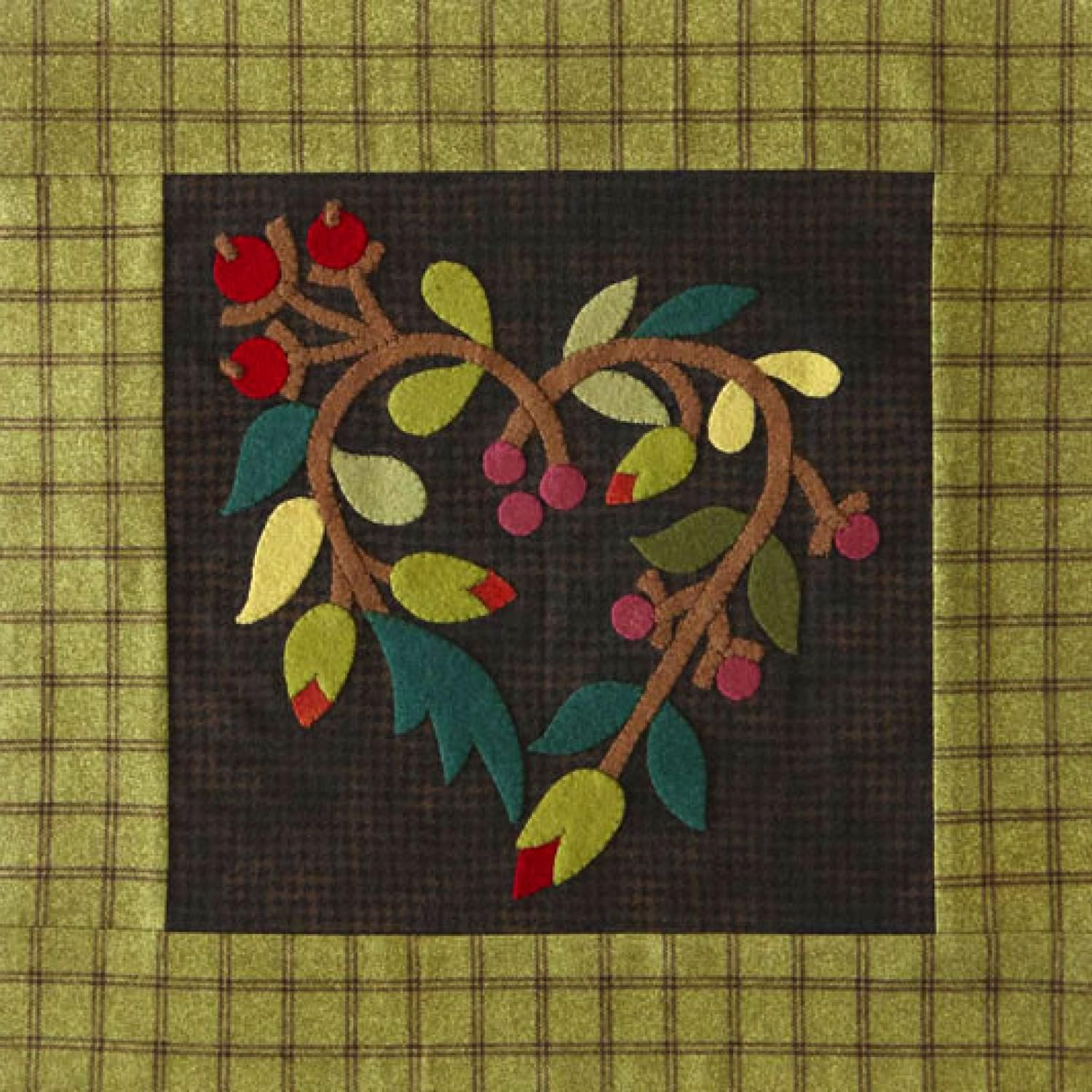 Warm the heart with a wall hanging made from felted wool and flannel. The appliqué shapes were cut from jewel-tone scraps and the houndstooth and plaid flannel is from the Woolies Flannel collection by Bonnie Sullivan for Maywood Studio.