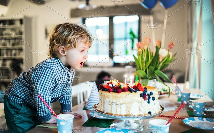 A boy standing on a chair blowing flower food cakes