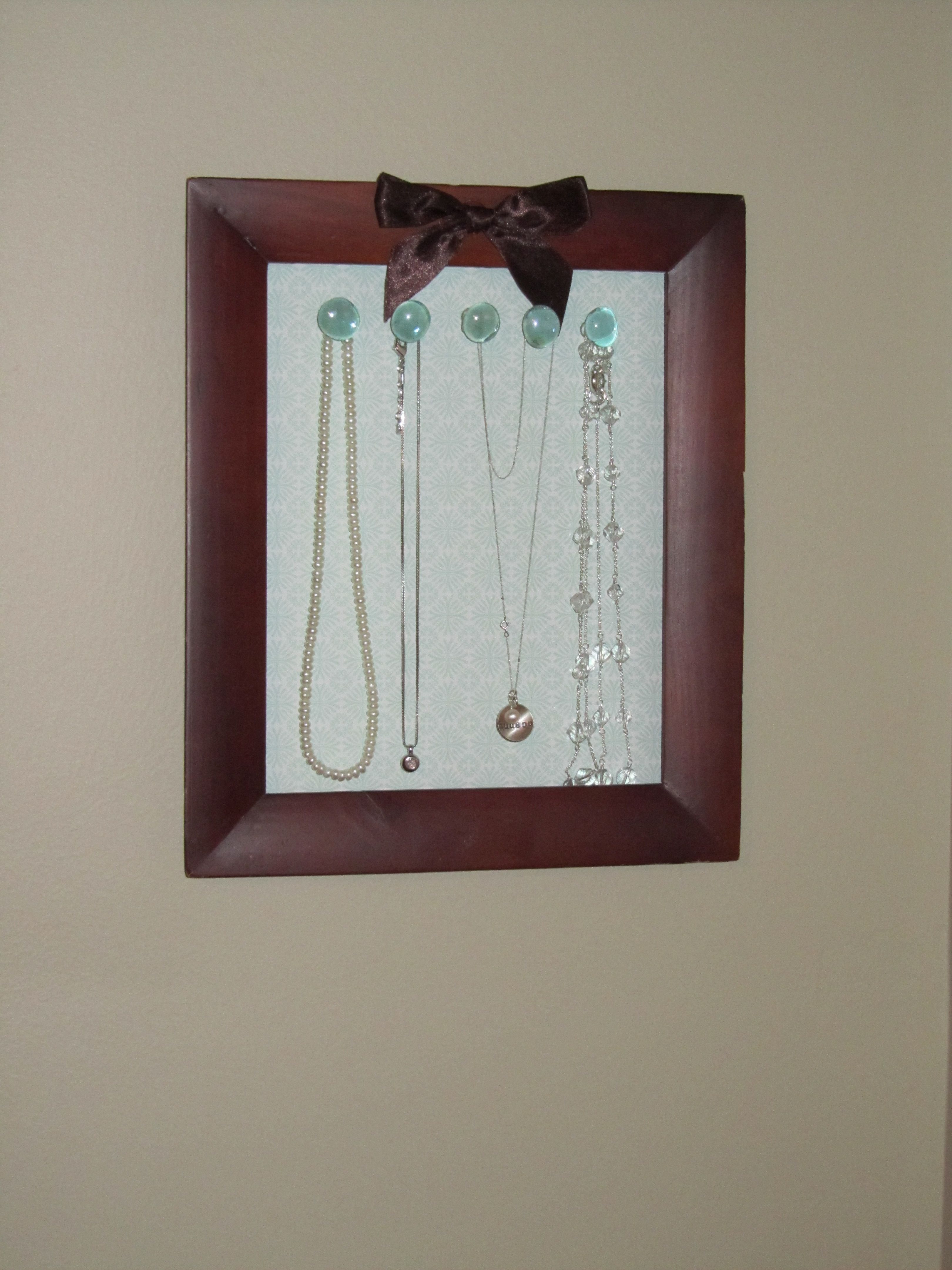 Necklace organizer.  This looks pretty easy - picture frame, craft paper, ribbon, glass beads and thumb tacks... and a handy dandy hot glue gun!    If this frame had a way to prop it up, this could be great for Premier shows.  :)