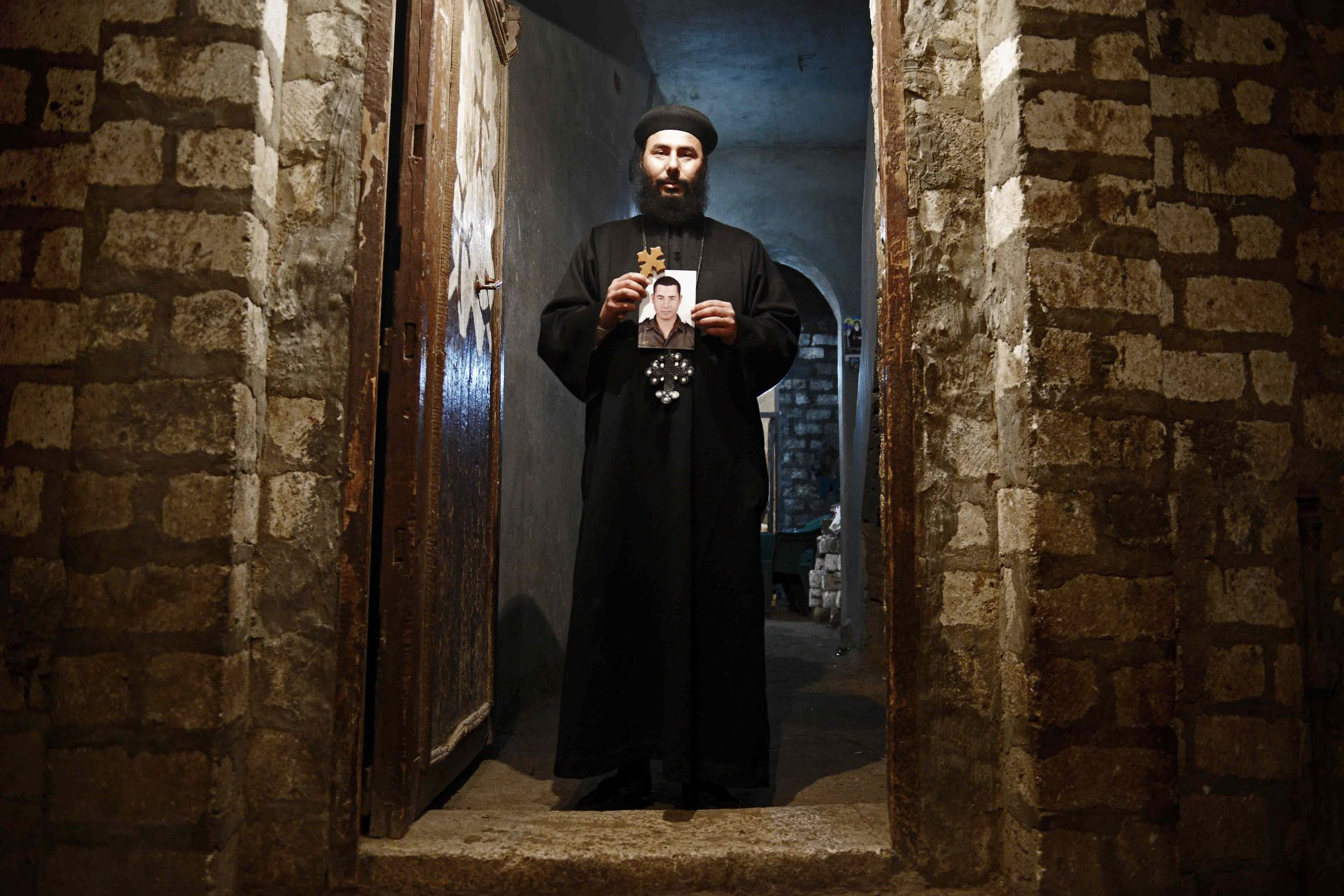 Picture of Bishop Botrous, uncle of 23-year-old slain laborer Mina Fayez by Jonathan Rashad | Town Al Aour, 13 of its residents were shown being beheaded in a video released by the Islamic State (ISIS). The town's victims were among 21 Coptic Christians whom ISIS says it beheaded after kidnapping them from migrant worker dormitories in Libya.