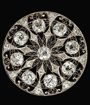 White gold circular openwork diamond brooch, Art Nouveau. Stunning white gold filigree brooch set with nine round Old Mine cut diamonds each weighing approximately 1 carat each and eight petite Old Mine cut diamonds. #FreemansAuction