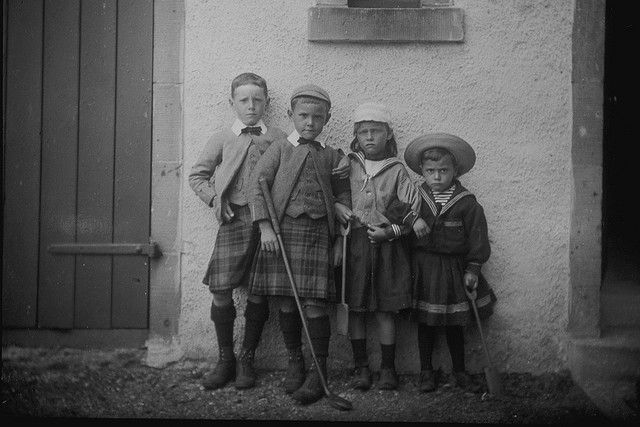 Look at their expressions!    These four children had their photograph taken during their school holidays at their home North Berwick. The family were the children of a general practitioner; the elder boys have been dressed in matching costumes and the younger boy and girl wear sailor suits, popular holiday attire at that period.    This image was printed from a 1/2 plate glass negative. The photograph shows four children posed against a wall. Left, two boys wear kilts with white collars and…