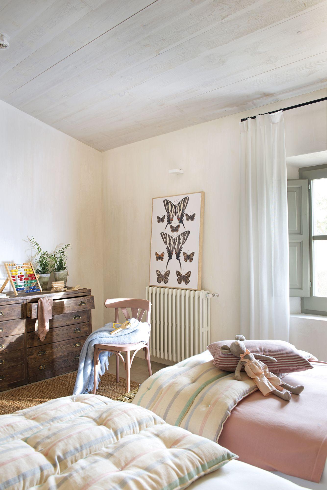 Cabecero de madera y taburetes como mesita de noche en el dormitorio ...