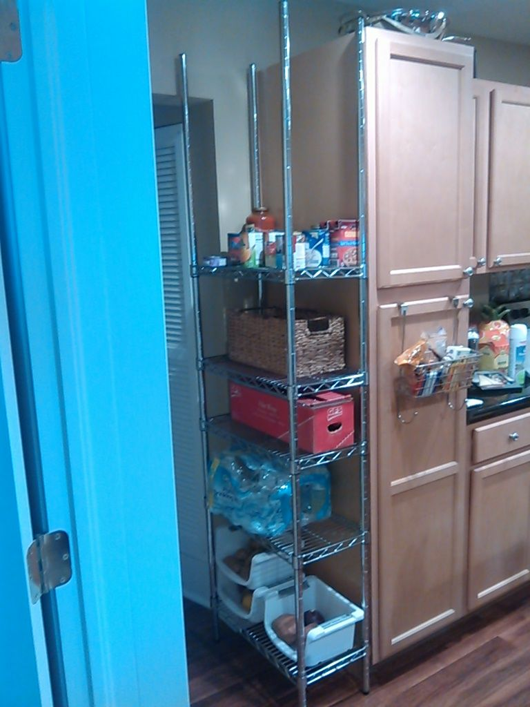 A narrow wire shelving unit used for the empty space between kitchen ...