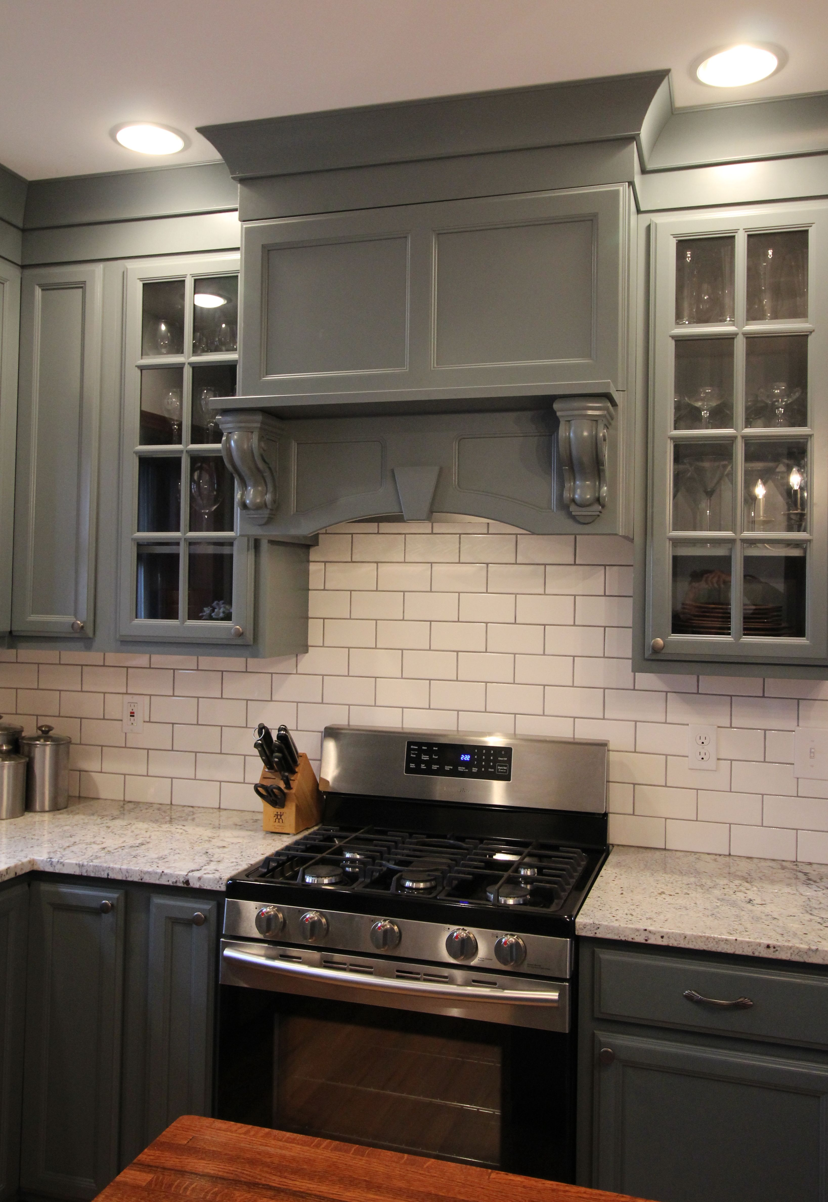 A custom range hood painted gray to match the cabinets that extend ...