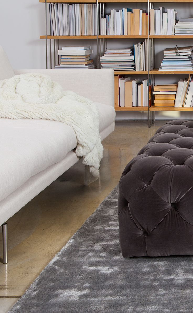 Modern comfort. Our cozy DIAMOND ottoman and SILKI rug contrast with our FLOAT sofa's steel legs.