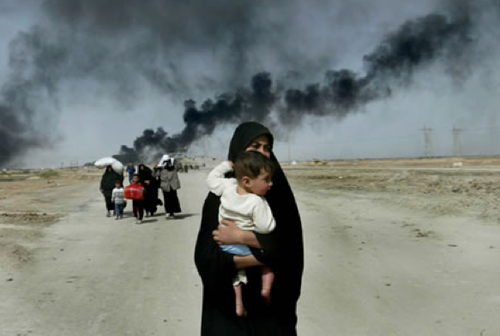 An Iraqi woman carries her young child on the outskirts of Basra as she flees with others from this southern Iraqi town Sunday, March 30, 2003. http://web.mit.edu/humancostiraq/photos.html