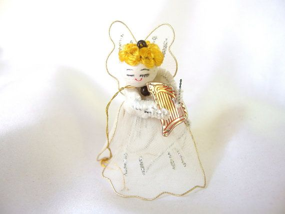 A vintage Christmas ornament, this white tulle angel has a red printed silver foil harp. She can be used as a feather tree topper, a package tie on, or a free-standing decoration. Her head is a hand painted wood bead with yellow hair, and her arms are chenille pipe cleaners. Gold hanging thread to hang from a tree, and white pipe cleaner to use as a tree topper or tie on.  She is 3 inches (7.6 cm) tall.  Condition: Very good. Check here for more items…