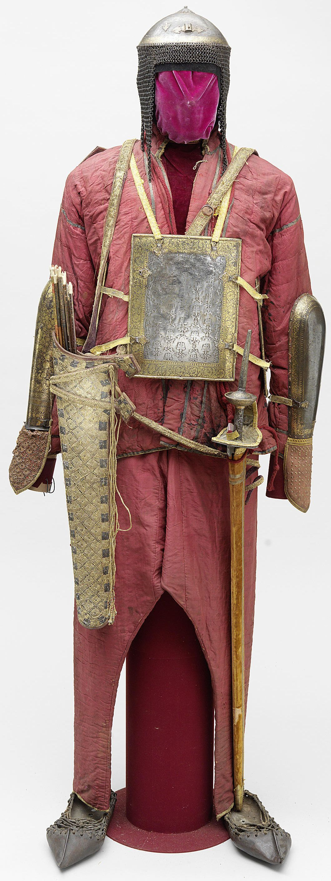 Indian khula-khud (helmet), char-aina (chahar-aina, chahar a'ineh), literally the four mirrors, chest armor with four plates, dastanas/bazu band (vambrace/arm guards), silk padded mail armour jacket and trousers, cotton padding covering a layer of steel mail, the inside lining decorated with small floral sprays on a cream ground, a pair of steel slippers with leather attachments, firangi sword, cloth quiver with arrows, jacket 74 cm. long, trousers 100 cm. long, end of the 18th century.