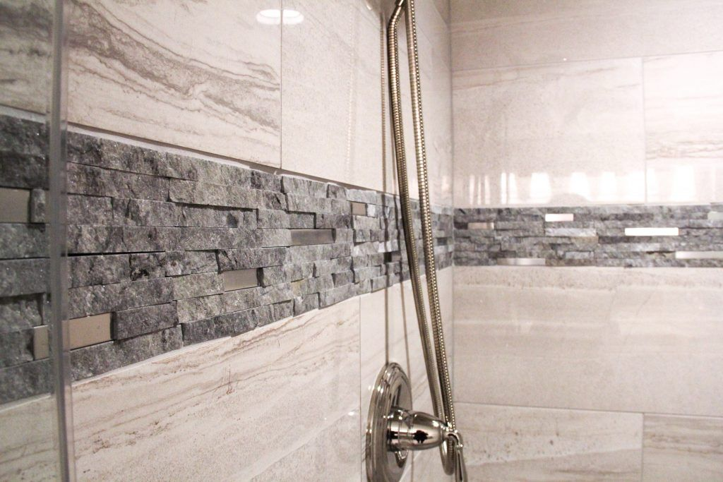 Shower Tile: Anatolia, Amelia: Mist Polished 12x24; Accent Tile: Eclipse Interlocking Mosaic.