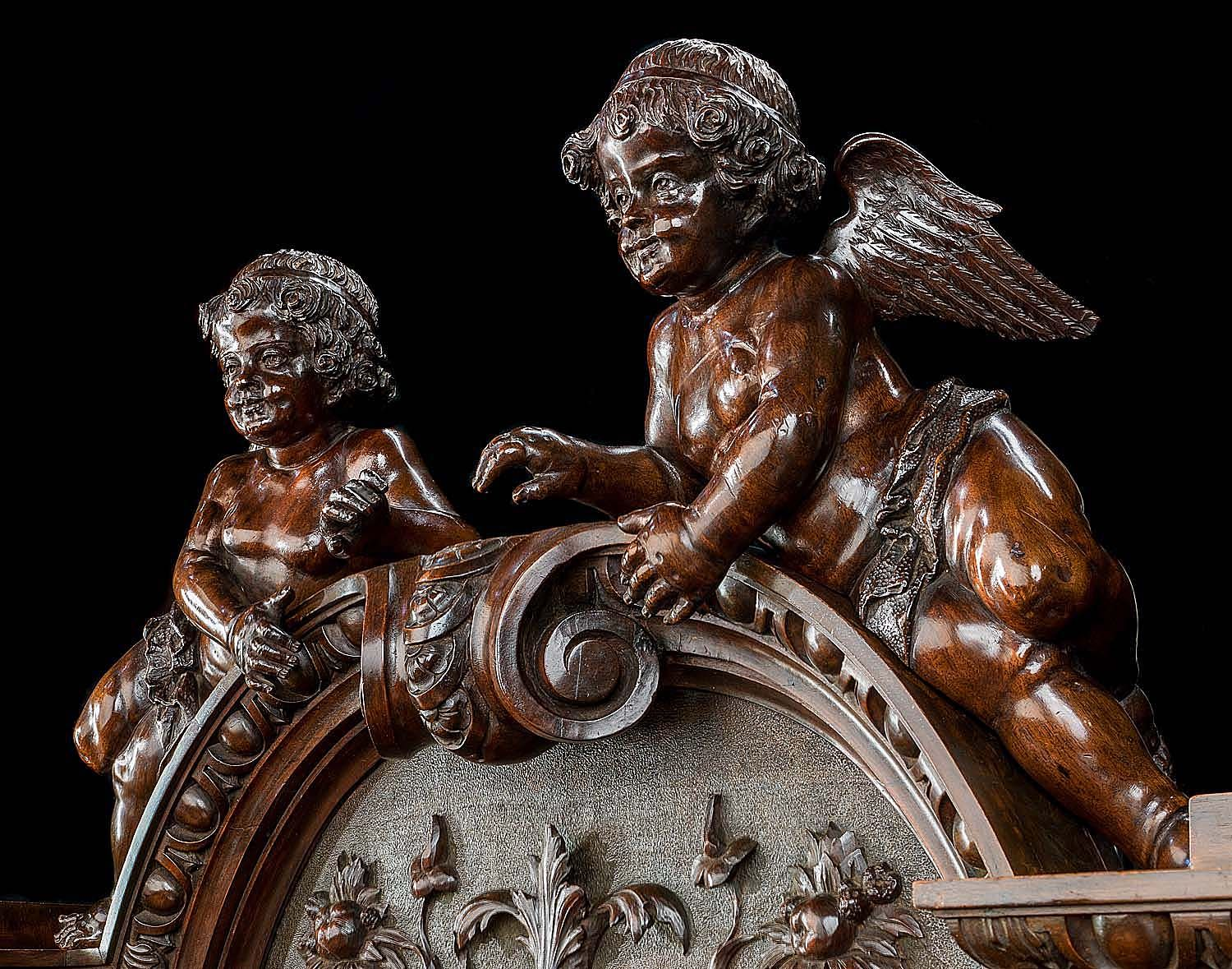 A Monumental Carved Walnut Sideboard in the early 17th century Venetian Baroque manner with a high arched back pediment surmounted by a pair of carousing cherubs above three ornate panels carved with mythical beasts, birds and scrolling foliage each flanked by four grand lion masks. The foliate decoration is echoed on the drawer fronts set above four powerful caryatid figures of Atlas and a pair of cupboards the doors, the recess and the sides of which are carved with detailed strapwork…