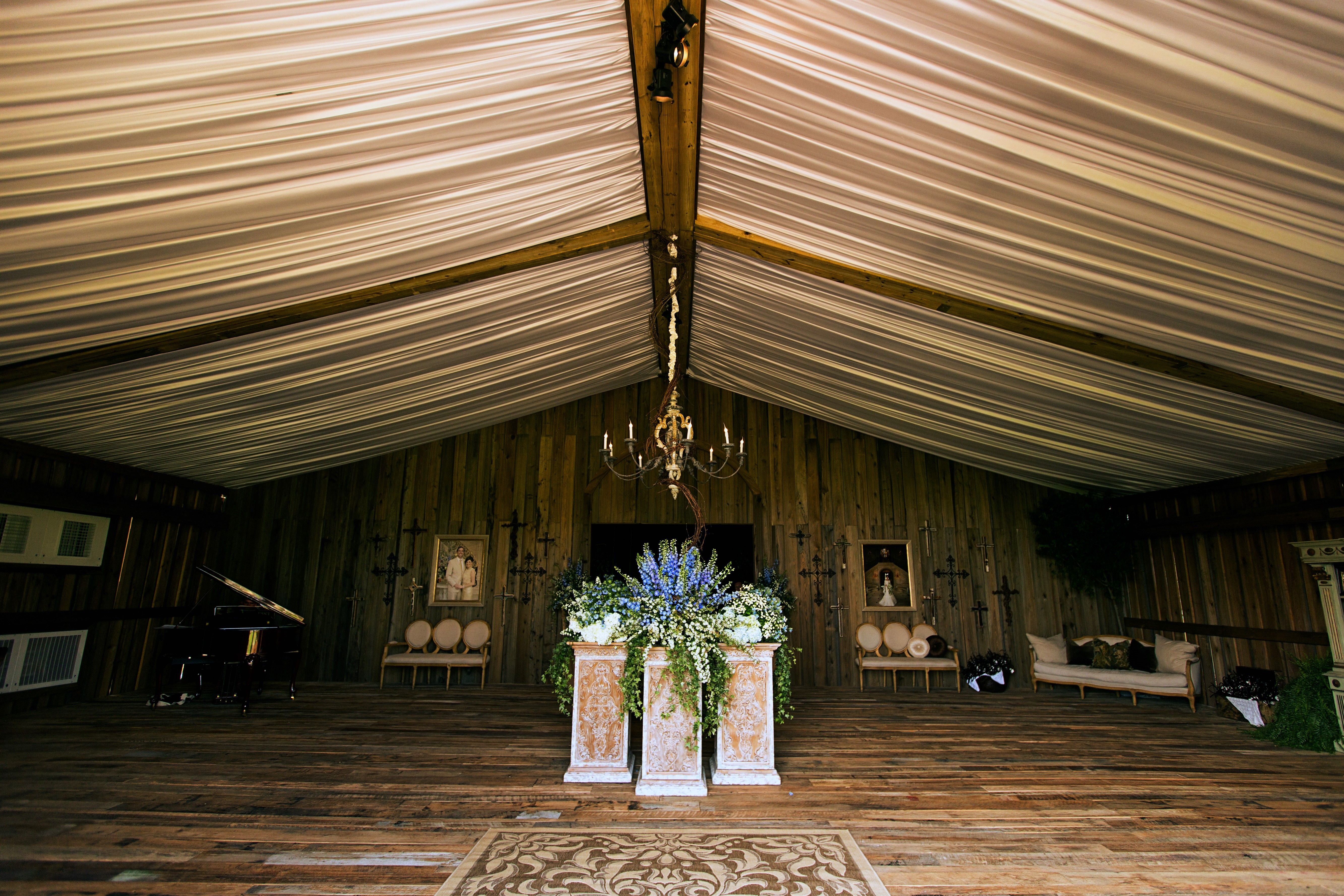 This was the grand entrance tent for a wedding reception. The custom wooden floors and walls were created from an old barn with white fabric covering the tents beam and ceiling.
