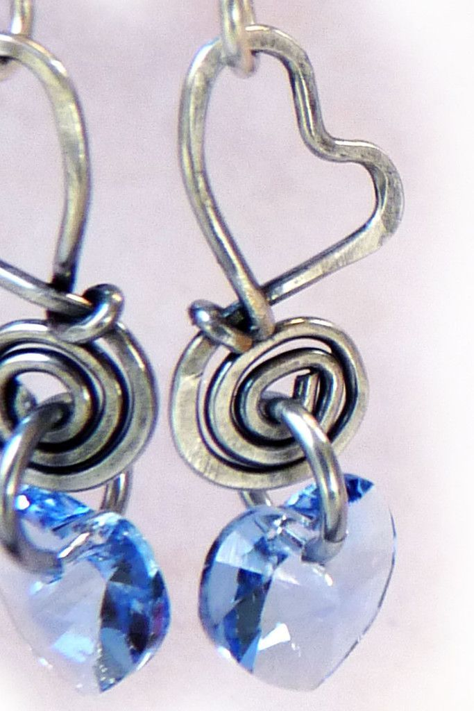 Sweet Hearts. Handmade dangle earrings created from cold forged, wire wrapped silver filled jewelry wire. Each expertly hammered heart is beautifully accented with a sapphire blue Swarovski heart. These earrings are perfect one-of-a-kind gift for your sweetheart. Very pretty. #valentine #valentinesday